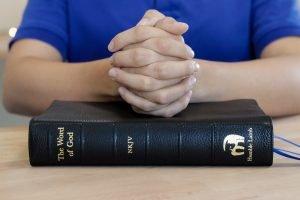 man praying with a bible